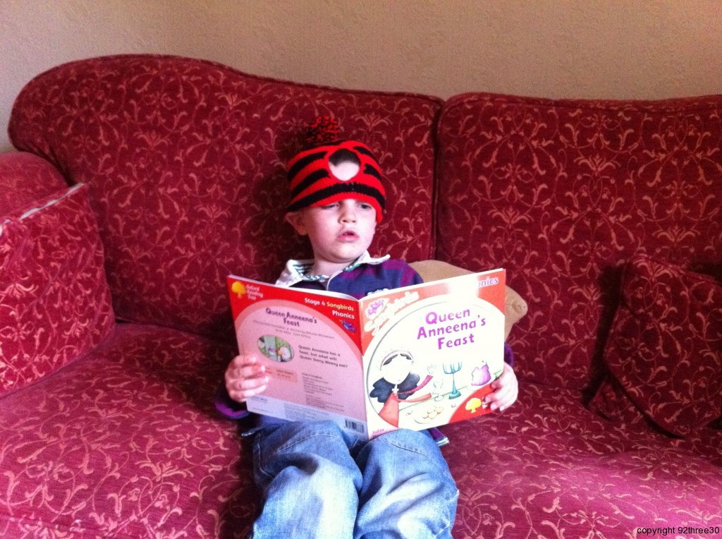Wearing a tea cosy reading oxford reading tree book