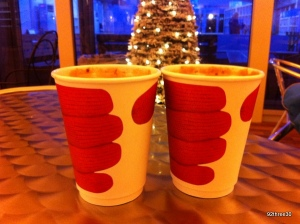 paper cups with gloved hands on