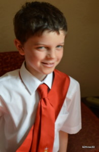boy wearing red tie and sash